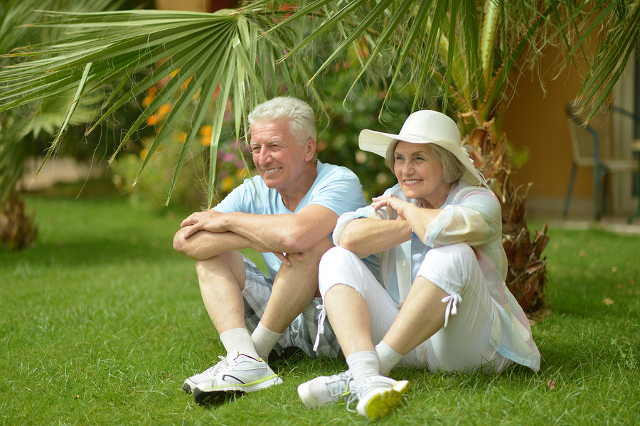 Happy senior couple sitting on green grass in Mission Viejo, CA