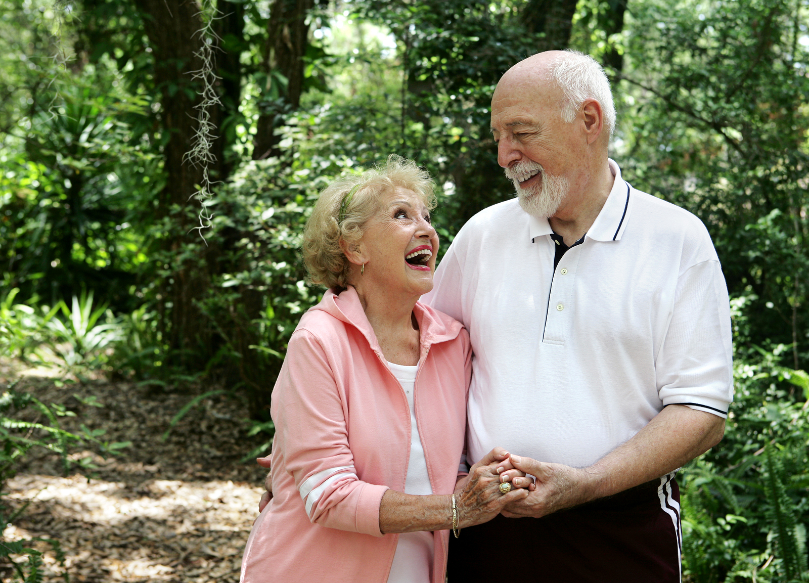 A happy active senior couple laughing together on a walk through the park in Laguna Hills, California.