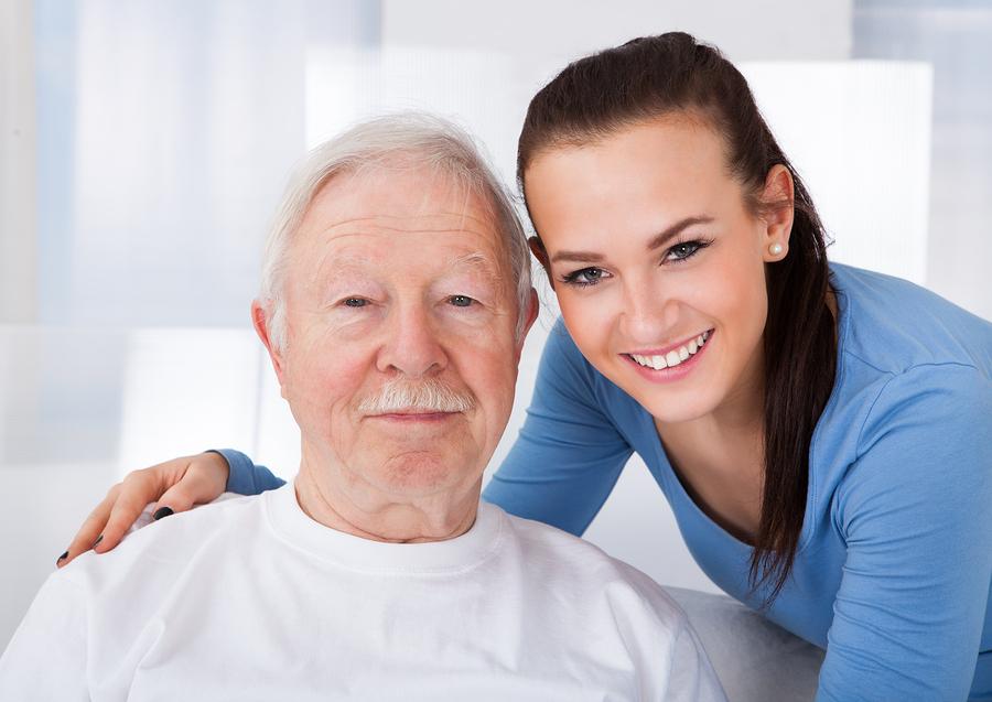 Portrait of young female caretaker with senior man at nursing home in Laguna Hills, CA