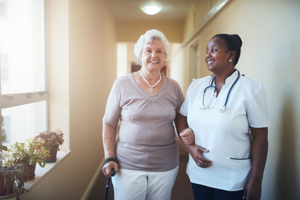 Happy healthcare worker and senior woman together at nursing home in Laguna Hills, California.