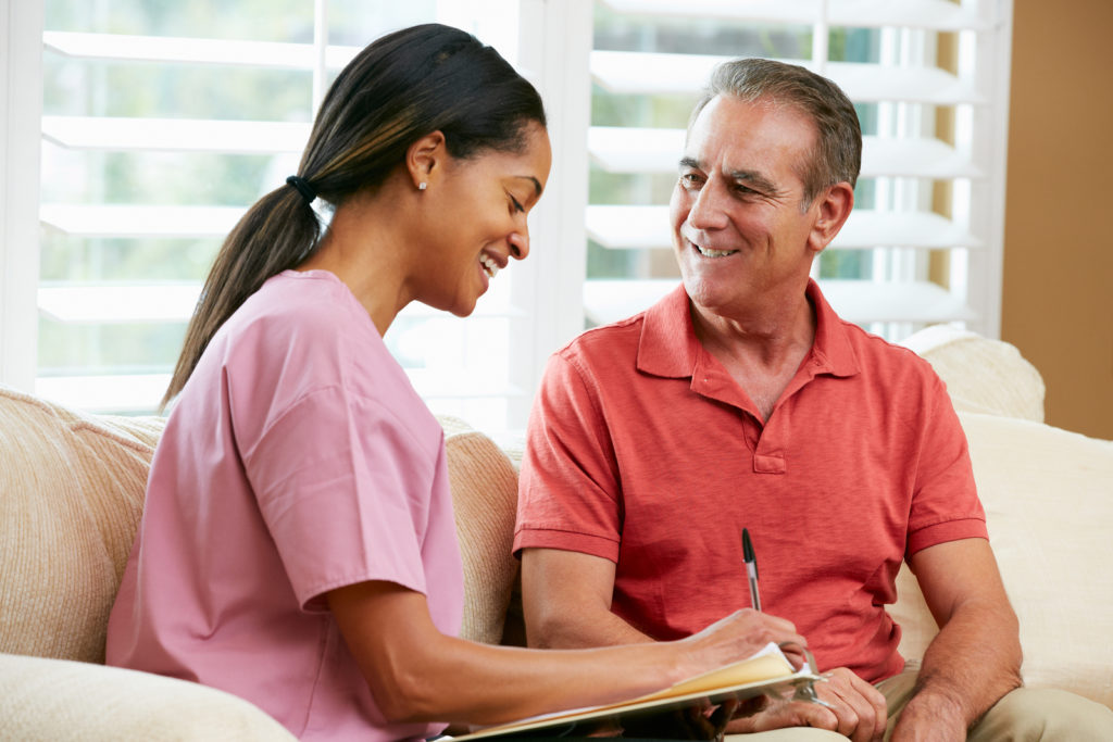 Nurse Discussing Records With Senior Male Patient During Home Visit in Laguna Hills, CA.